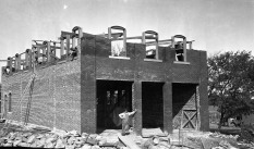 Construction began on the Kratzer Brothers' Mercantile at Volland, Kansas in 1912 and the store opened for business in October of 1913. A mason is seen here, standing in front of the brick framework of the store.