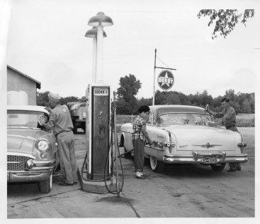 In this photograph dated October 30, 1955 Ross Brown, left and Marie and Paul Brown are seen fueling and servicing cars at their service station in Harveyville. Ross Brown opened the station on October 25, 1941.