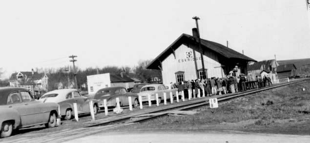 A crowd waits for a train at the Eskridge ATSF depot in this early 1950s photograph. Notice the Eskridge Star Grange to the left of the depot in this view and Dr. Coffey's house at the far left.
