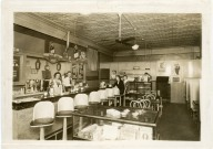 This is the second of two interior views of an Alma, Kansas soda shop and eatery. A 1944 calendar is hanging on the back wall.