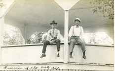 "This real photo postcard, circa 1910 shows two men sitting on the railing of the bandstand, located in the City Park of Eskridge, Kansas. Handwritten at the bottom of the photo is ""remains of the dirty six."""