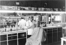 Bat Nelson gives a customer a haircut at Nelson's Alta Vista barbershop in this view from the 1970s.