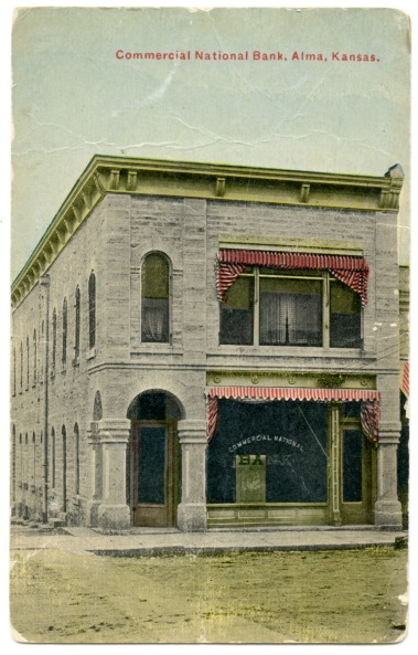 This is a colorized photo postcard showing the Commercial National Bank in Alma, Kansas. This building, a former saloon, was purchased by Louis Palenske in 1907 and the façade was extensively remodeled to accommodate the new bank.