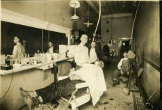 Glen Loveland, who operated this barbershop in Eskridge, Kansas between 1920 and 1930, prepares to shave one of his customers. Loveland later began working for the U.S. Post Office, closing his shop, but continued to barber on Saturday nights at Bill Wakefield's barbershop in Eskridge.
