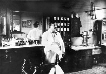 George Woody stands next to his barber chair at his shop in Paxico, Kansas in this view, circa 1905, by Alma photographer, Gus Meier. Photo courtesy Kansas State Historical Society, Kansasmemory.org.