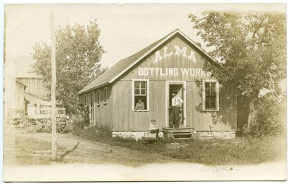 James Barger, in doorway, his wife, Dorthea, peering out the window, and their son, Norman, pose for this real photo postcard at their Alma Bottling Works plant in Alma, Kansas, circa 1908.