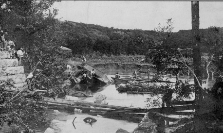 Men survey the remains of a locomotive in the bed of Mill Creek where it fell as a bridge collapsed due to flood waters. Remains of the locomotive are still visible in the creek bed.