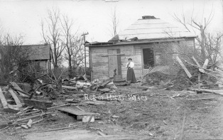 Mrs. Henry Meyers stands outside the remains of the Meyers home located in East Eskridge, shortly after the 1911 tornado hit the city. Mrs. Meyers holds a cat in her arms.