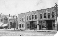 This real photo postcard view shows the business district of Alma, Kansas, located on the west side of the 300 block of Missouri Street. The buildings, identified from right to left, are, The Signal office, Dr. G.W.B. Beverley's office, The Enterprise office, Undorf's Meat Market, and Weaver's Abstract. This photo view dates from about 1908.