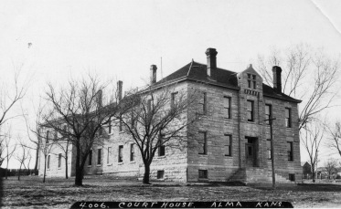 The Wabaunsee County Courthouse is seen in this real photo postcard created by Zercher Photo in about 1910. At the far left of the image at the rear of the building one can see the top of the fence surrounding the rock pile. The County Jail was located in the back portion of the building.