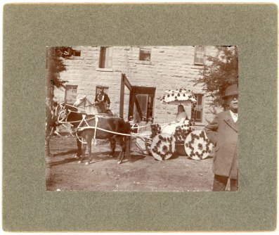 "Miss Minnie Palenske drove a ""Tom Thumb"" carriage decorated with red roses and pulled by a team of Shetland ponies in the 1900 Woodman Parade. Palenske's carriage is seen here in front of the Commercial Hotel, waiting for the parade to begin. The man on horseback wears a Woodman uniform."