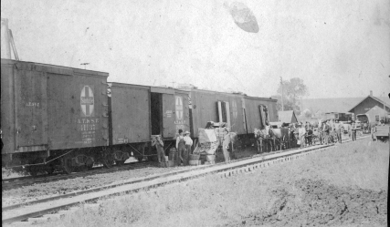 Merchants and residents of Eskridge, Kansas unload freight from an Atchison, Topeka, and Santa Fe Freight train at the Eskridge depot in this view, circa 1900.