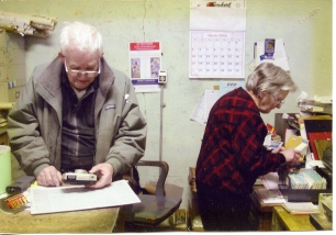 Dean Dunn holds a camera behind the counter of Dunn Home Supply while Inez Dunn, City Clerk, records utility bill payments in this view from March of 2002.