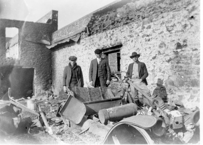 Three unidentified men stand amid the burned-out wreckage of autos at R. C. Day's Ford dealership in this photo taken on February 4, 1921.