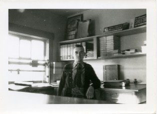"Leland Lucky stands in the ""front office"" of the Clinton Scott Lumber Company at Eskridge in this view from the 1930s."