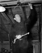 Grandpa Hoots, Carl E. Hoots, wires a building at Fort Leonard Wood during World War II.