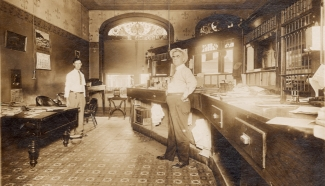 Oliver W. Hess, left and J. R. Henderson stand behind the teller's cages in the Alma National Bank located at 311 Missouri Street in Alma, Kansas in this view from 1911. Photo courtesy Alan Hess.