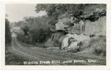 This real photo postcard looks north on K-4 Highway, two miles north of Dover, Kansas. The Highway crosses Mission Creek at the bottom of the hill.