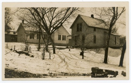 The M. E. Church and Parsonage at Dover, Kansas are seen on this real photo postcard by Zercher Book and Stationery, circa 1910.