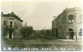 This real photo postcard shows the Alma Hotel on the left and the Bank of Alma on the right in a view from about 1910. Today this street is East 4th Street.