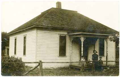 This real photo postcard, postmarked 1910, shows a woman and two children standing in front of their home in McFarland, Kansas.