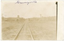 This 1908 real photo postcard looks down the ATSF railroad tracks leading into Harveyville, Kansas. Notice the depot and grain elevator on the left side of the tracks.