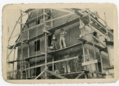 Friedrich Meditz, top row, right, stands on scaffolding of a residence in Villach being reconstructed after Allied bombing during World War II. Notice that the hod-carrier standing next to Fred is a female, and another stone mason stands on the lower level.