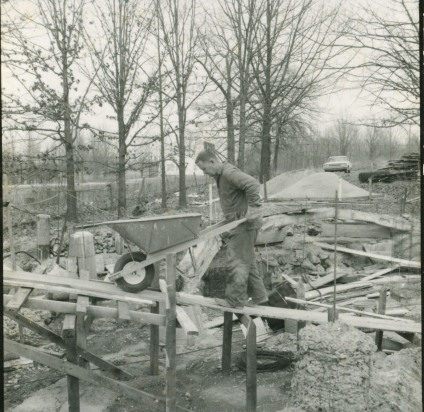 Carl Hoots wheels a load of cement as construction begins on the cave at Ozarka Village in January of 1969.