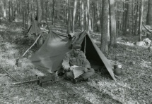Fred Meditz sits in front of his tent during maneuvers near Neu-Ulm, Germany while in the U.S. Army, circa 1956.