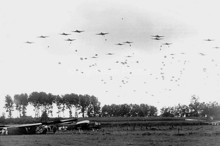 Members of the 82nd Airborne Division begin parachute to the ground in Holland in September of 1944. Notice the gliders already on the ground.