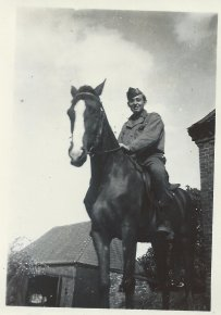 Charlie Barnhart is photographed on horseback while rounding-up German prisoners in Sachau, Germany, 1945.