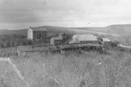 This 1890s photo by Gus Meier shows a typical evolution of the Wabaunsee County farm. Notice the log building to the right of the two-story stone house. It's likely that it was an original homestead cabin. In the foreground, log outbuildings are visible at both ends of the livestock lots. Notice the thatched roof on the long loafing shed. Photo courtesy Paul Gronquist