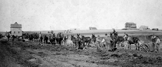 Workers driving mule teams pulling slips level the road bed for the CRIP railroad line at Alta Vista in this view from 1887. Notice that the first depot at Alta Vista, seen at the far left, had been constructed before the rails had ever been laid. At the far right on the horizon, the Fairview Hotel is visible under construction.
