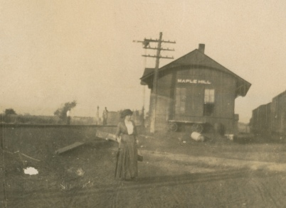 A passenger on the Rock Island railroad poses for a photo in front of the Maple Hill, Kansas depot, circa 1900.