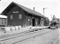 A railroad station agent waits on the platform with a mailbag as a CRIP train arrives at the Volland, Kansas depot, circa 1905.