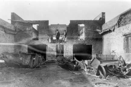 Three unidentified men stand inside the ruins of the R. C. Day garage after a fire destroyed the business on February 4, 1921. The ruins of burned Ford cars are visible in the foreground. Photo courtesy the Dean Dunn Collection.
