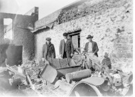 Three unidentified men stand behind the rubble of a burned Ford at the R. C. Day Garage in Eskridge, Kansas. Photo courtesy the Dean Dunn Collection.