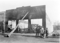 Spectators view the ruins of the R. C. Day Garage after the February 4, 1921 fire which destroyed the business. Amazingly, the brick storefront, seen here braced with a telephone pole, was salvaged and stands today at 212 S. Main Street in Eskridge, Kansas. Photo courtesy the Dean Dunn Collection.