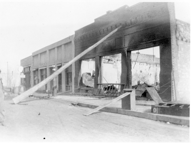 It was nothing short of miraculous that the four businesses located just to the north of Day's Garage survived after the February 4, 1921 fire which destroyed 17 autos at the Ford dealership. Businesses seen in this view, from right to left are Day's Garage, Robertson Paint and Wallpaper, Wright Barber Shop, the Cozy Cafe, and Waugh Implement Company. Photo courtesy the Dean Dunn Collection.