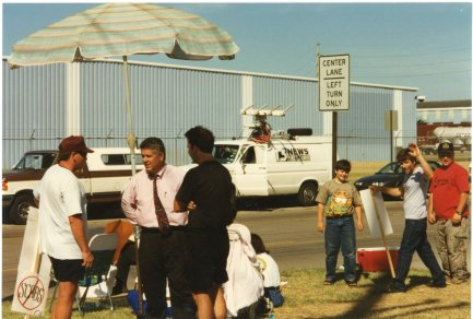 News crews frequented the strike lines in Topeka during the 1997 UPS strike. In the foreground, UPS center manager, Rod Ruggles (wearing a tie) speaks with a striker.