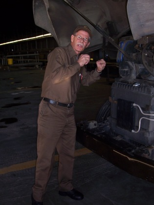 UPS package car driver, Tom Shehi checks the oil on his package car on his final day of work before retirement.