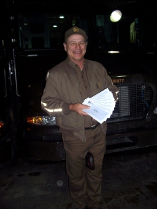John Hertlein, longtime UPS package car driver in the Topeka center, shows his final eight paychecks on his last day of work in the Topeka UPS center.