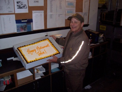 John Hertlein poses with his retirement cake on his last day of work at the UPS package center in Topeka.