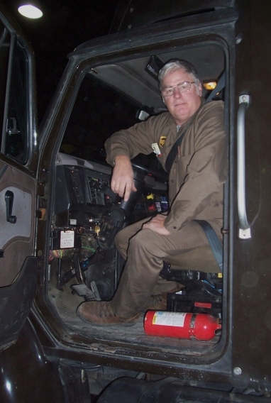 Topeka feeder driver, Mike Garrett pauses for a moment for a photo from the cab of his tractor in the UPS center.