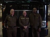 Topeka feeder drivers, (left to right) Terry Manspeaker, Bob Kramer, and Clarence Banks pose in front of a tractor inside the UPS building in Topeka.