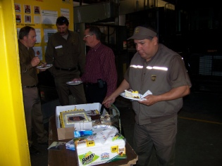 UPS employees, (left to right), Jim Figgs, Lynn Thompson, Dave Brown, and Bobby Munoz share a piece of cake on Christmas Eve, 2012, celebrating the retirement of Greg Hoots.