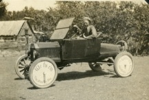 "Elmer Steinmeyer poses for his sister, Selma Steinmeyer's camera in a boattail roadster at the family's farm, located five miles south of Alma. Notice the wheel covers, advertising, ""We fix 'em"" and ""The Alma Tire Shop."" Photo courtesy Keith Schultz"