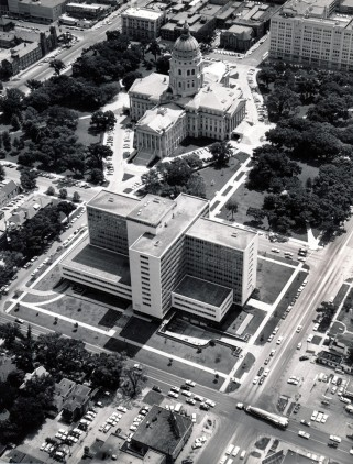 An Atlas missile, visible in the lower right hand corner, passes north through the intersection of SW 10th and Topeka Blvd. in this 1961 view. The State Office Building and the State Capitol are visible in the center of the photo.