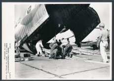 Workers lay a steel track into the cargo area of a C-133 transport plane to remove an Atlas missile in the cargo bay. This view is dated 6-29-61.