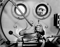 This award-winning photograph by GDA photographer Dave Mathias shows an engineer testing pneumatics. Mathias was inside the pressure tank when this 1961 view was taken.